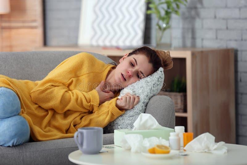 Jovem mulher doente que sofre do frio no sofá em casa fotografia de stock royalty free