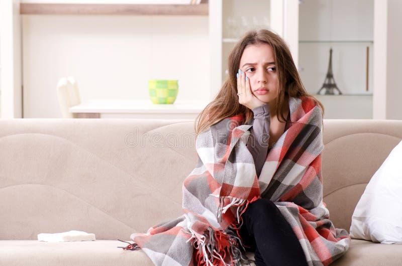 A jovem mulher doente que sofre em casa imagem de stock