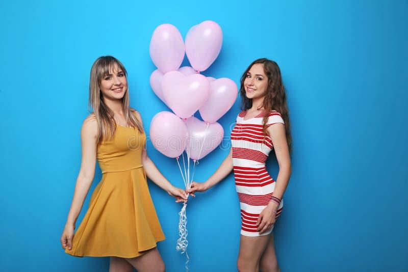 Jovem mulher dois com balões do coração fotografia de stock