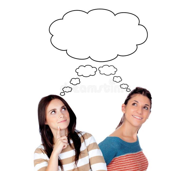 Jovem mulher dois que pensa a ideia mais ou menos idêntica fotografia de stock