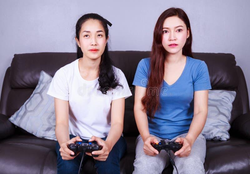 Jovem mulher dois que usa o controlador do manche que joga o jogo de vídeo sobre fotos de stock