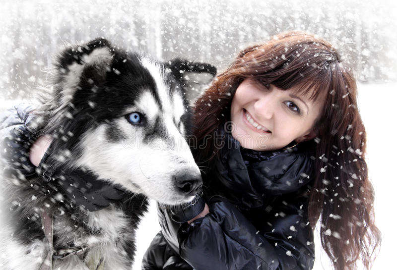 Jovem mulher e cão de puxar trenós siberian na neve imagens de stock royalty free