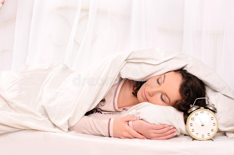 Jovem mulher e despertador de sono foto de stock royalty free