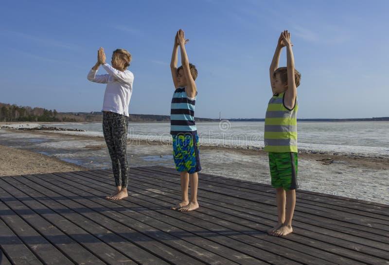 Jovem mulher e duas crianças que praticam a ioga na praia fotografia de stock royalty free