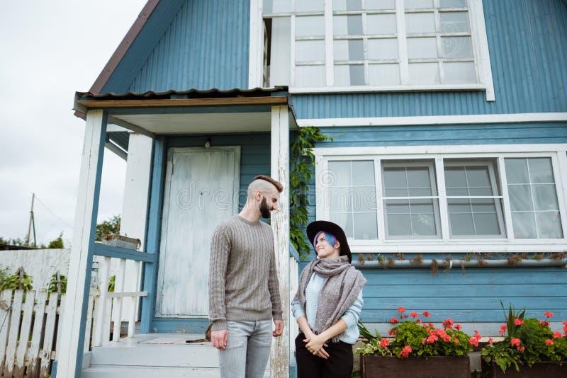 Jovem mulher e homem, família, sentando-se no patamar da casa da vila com abóboras imagens de stock royalty free