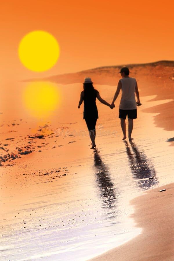 Jovem mulher e homem no amor que andam em conjunto na praia com por do sol bonito imagem de stock