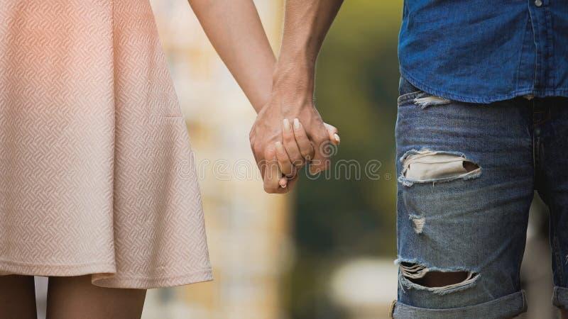 Jovem mulher e homem que guardam as mãos, relacionamento macio de pares doces, amor imagens de stock