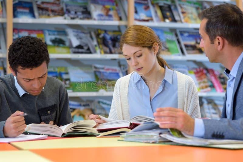 Jovem mulher e homens na biblioteca fotografia de stock