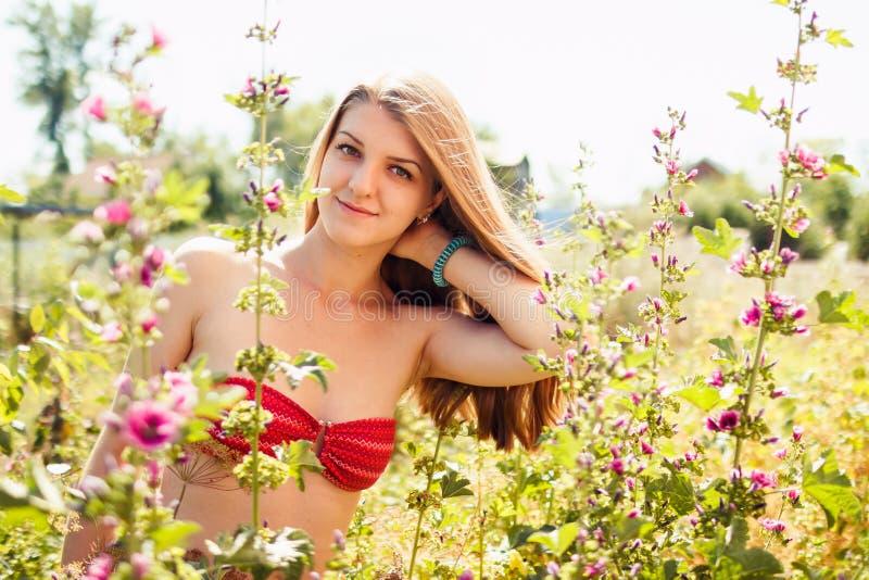 Jovem mulher e malvas bonitas imagens de stock royalty free