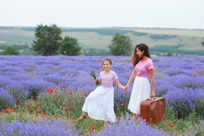 A jovem mulher e a menina est?o andando atrav?s do campo de flor da alfazema, paisagem bonita do ver?o imagem de stock