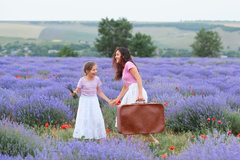 A jovem mulher e a menina est?o andando atrav?s do campo de flor da alfazema, paisagem bonita do ver?o imagens de stock royalty free