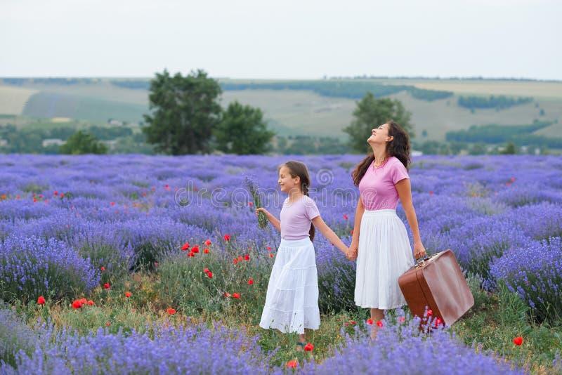 A jovem mulher e a menina est?o andando atrav?s do campo de flor da alfazema, paisagem bonita do ver?o foto de stock royalty free