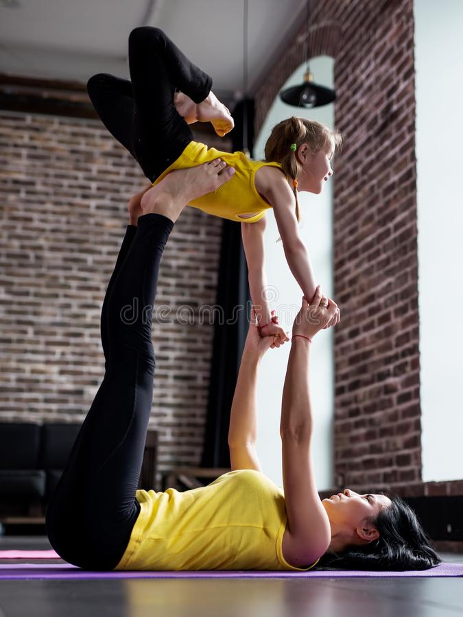 A jovem mulher e a menina que fazem o voo da ioga do sócio levantam o exercício junto fotografia de stock royalty free