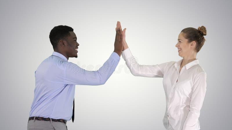 A jovem mulher e o homem novo na roupa formal dão altamente cinco no fundo do inclinação foto de stock