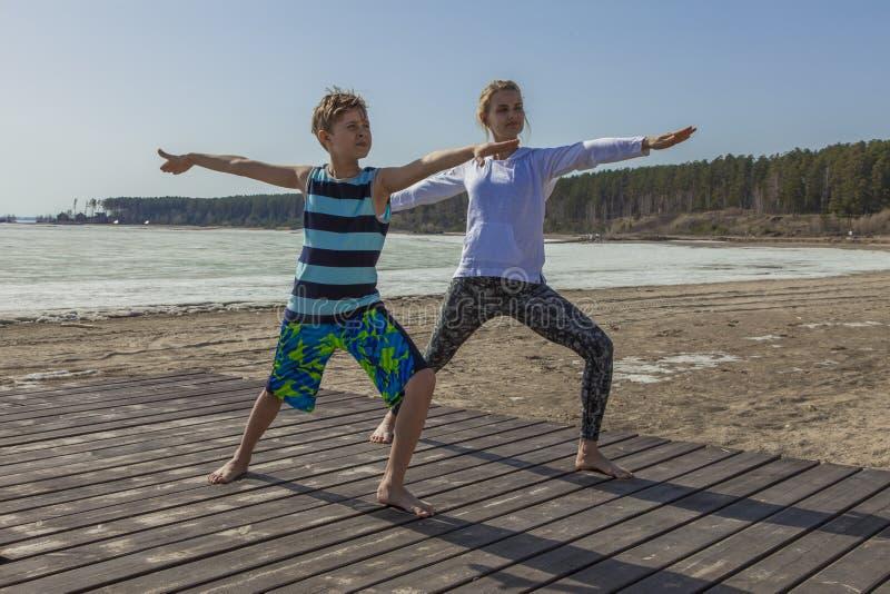 A jovem mulher e o menino que estão na ioga levantam na praia imagens de stock royalty free