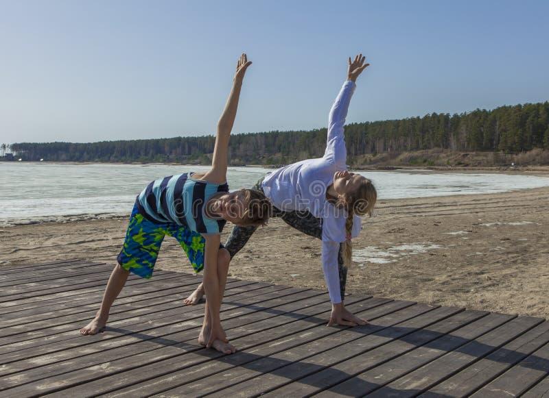 A jovem mulher e o menino que fazem ângulo lateral prolongado levantam fotografia de stock royalty free