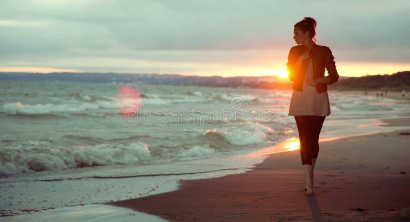 Jovem mulher e o por do sol no fundo fotos de stock