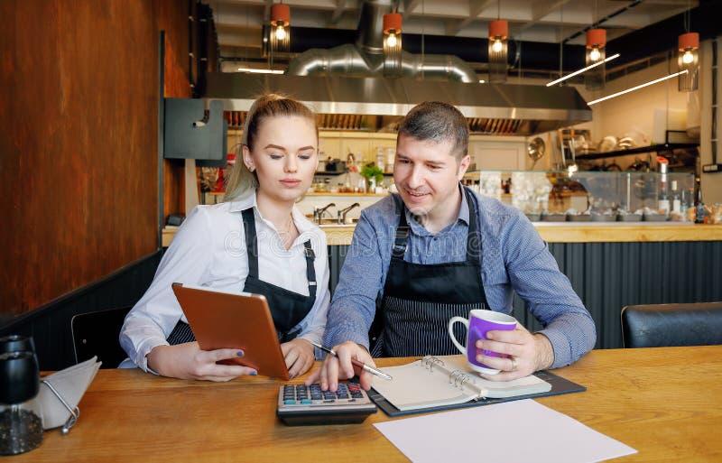 A jovem mulher e seu marido que sentam-se na tabela com fazer da tabuleta e dos papéis amarrotados esclarecem seu restaurante peq imagem de stock