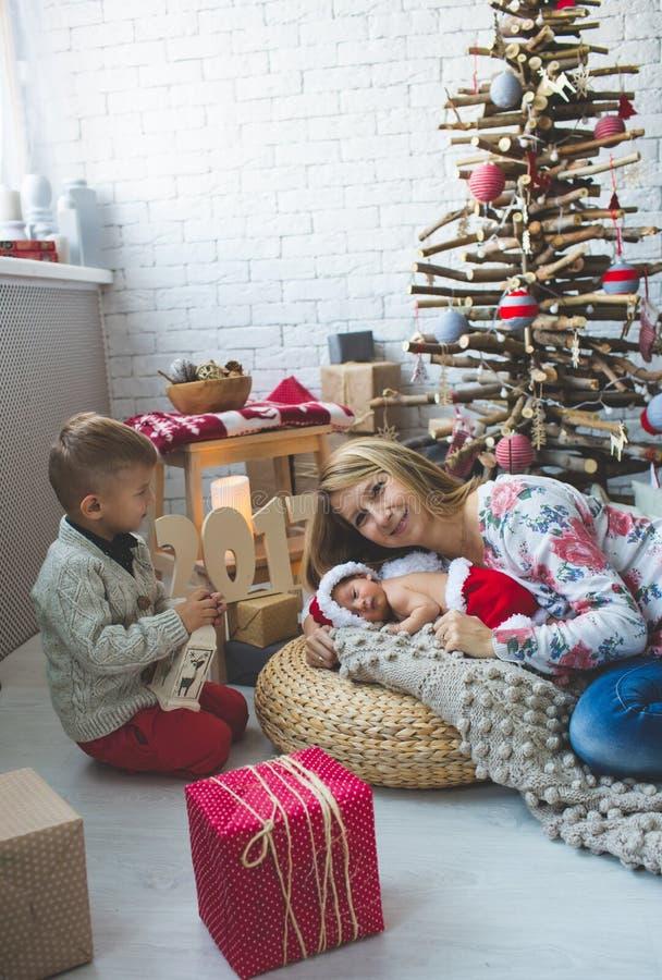 A jovem mulher e seus bebês aproximam a árvore do xmas da forma imagem de stock