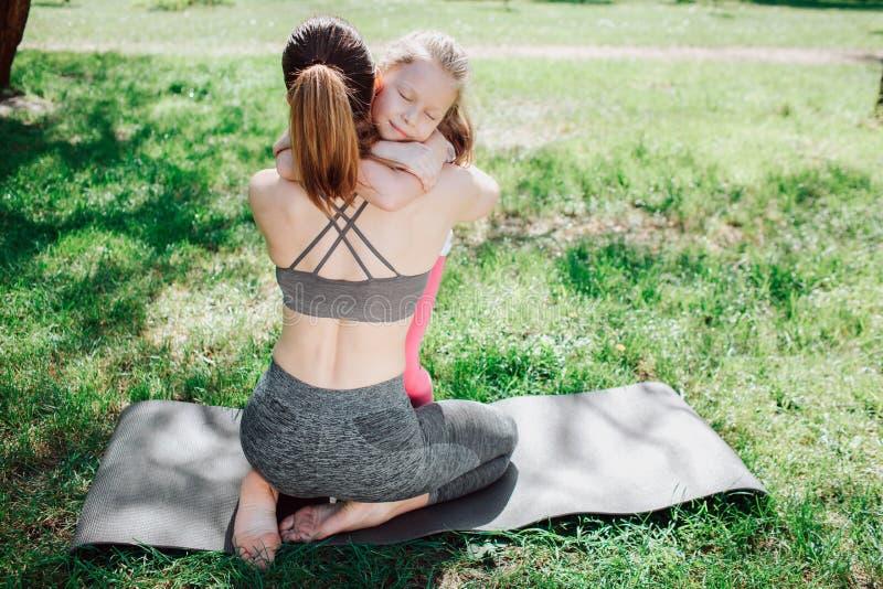 A jovem mulher e sua filha estão abraçando-se Ambos eles estão sentando-se no carimate na grama verde Há um arquivo de imagens de stock royalty free