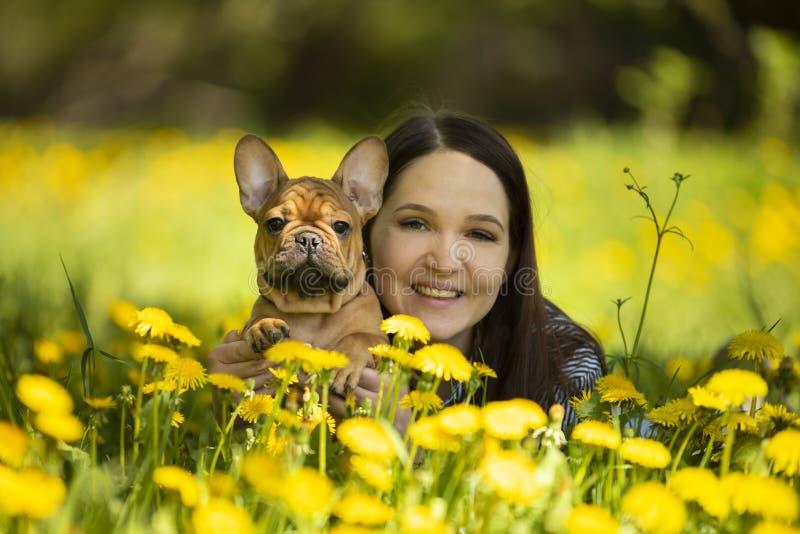 A jovem mulher e um cachorrinho do buldogue franc?s est?o descansando em um parque fotos de stock royalty free