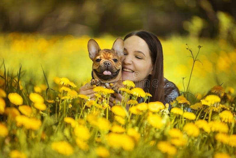 A jovem mulher e um cachorrinho do buldogue franc?s est?o descansando em um parque fotografia de stock royalty free