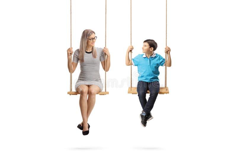Jovem mulher e um rapaz pequeno nos balanços que olham se foto de stock