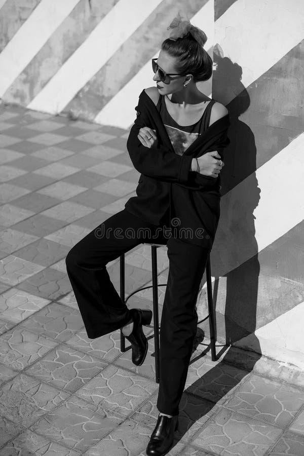 A jovem mulher elegante bonita está sentando-se em uma cadeira perto da parede listrada fotos de stock royalty free