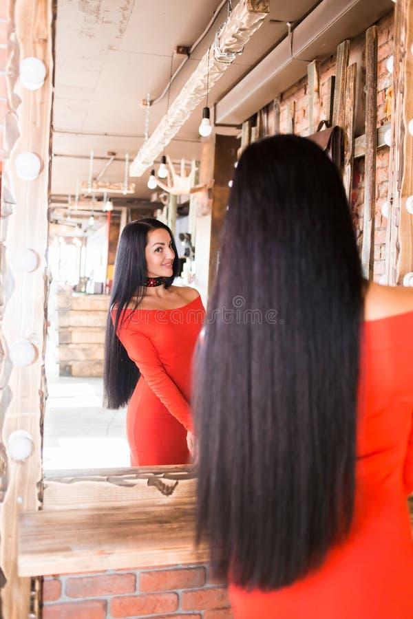 Jovem mulher elegante bonita no salão de beleza que olha no espelho após a composição e os cuidados capilares Menina no sorriso v foto de stock