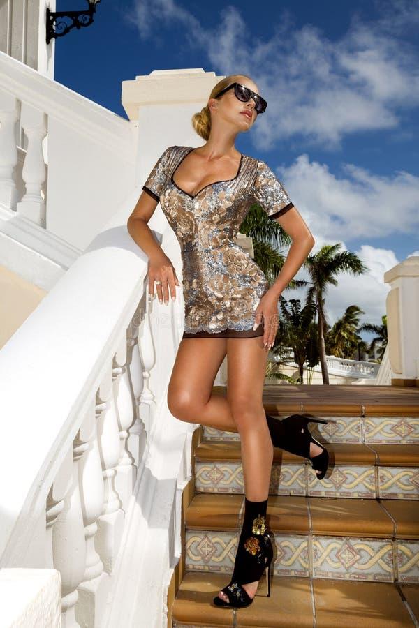 A jovem mulher elegante bonita que levanta no parque, óculos de sol, seqines veste-se, os saltos altos, cabelo louro Foto do ver? fotos de stock