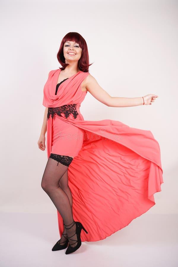 Jovem mulher elegante com corte de cabelo do prumo da cor de cobre no vestido longo da noite coral da cor no fundo branco no estú foto de stock
