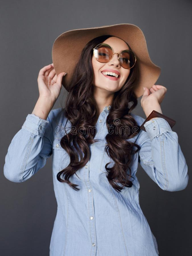Jovem mulher elegante da felicidade, levantando no estúdio, toques com mãos seu chapéu, em um fundo cinzento fotografia de stock royalty free