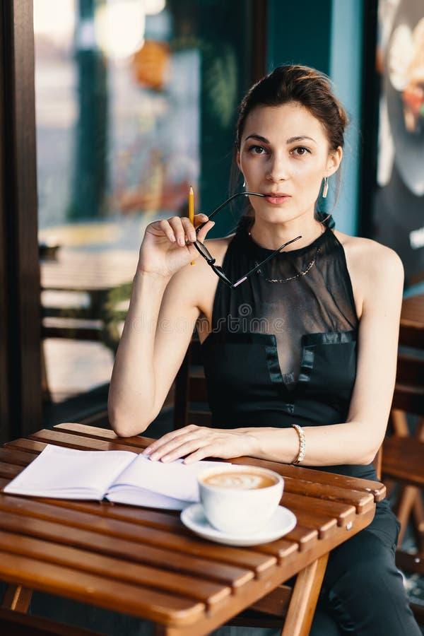 A jovem mulher elegante decolou seus vidros ao tomar uma ruptura de fotografia de stock royalty free