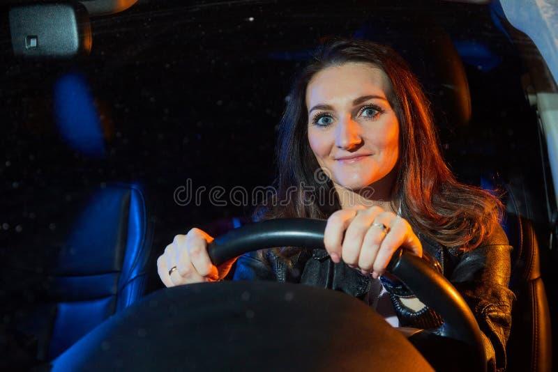 Jovem mulher elegante em um carro na noite e para colorir a luz que behing a foto de stock