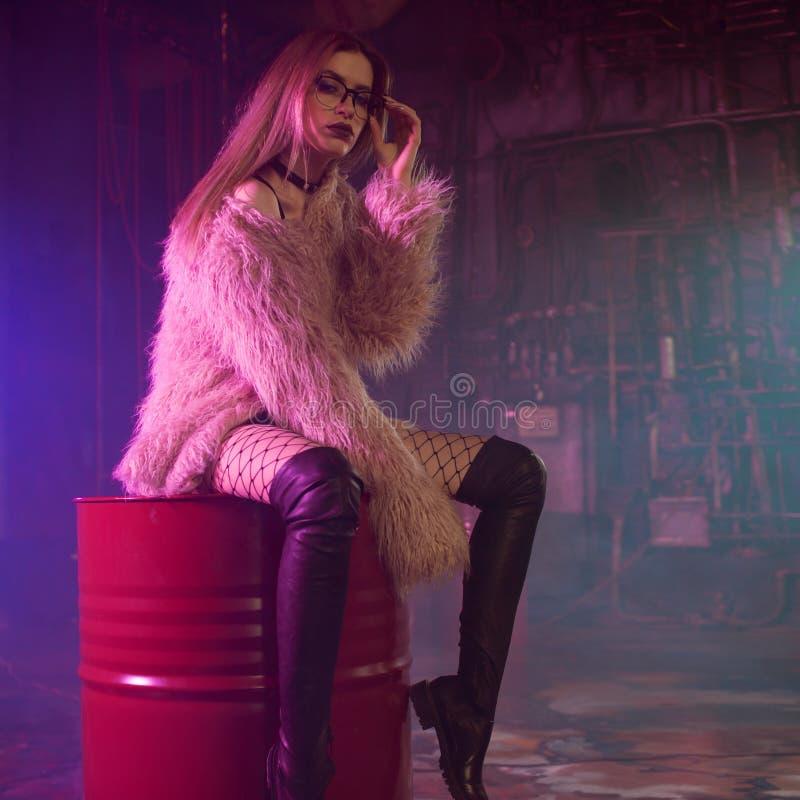 Jovem mulher elegante em um revestimento cor-de-rosa macio, luz de néon fotos de stock