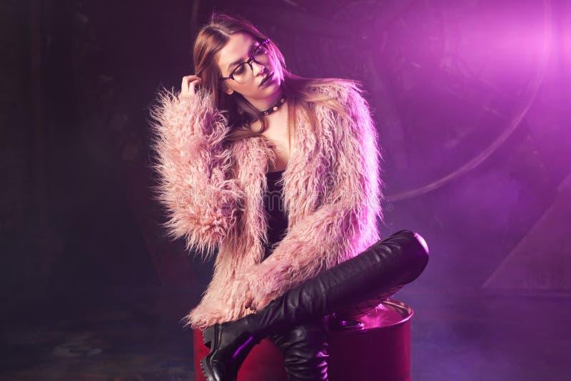 Jovem mulher elegante em um revestimento cor-de-rosa macio, luz de néon Retrato de uma menina na moda bonita fotografia de stock royalty free