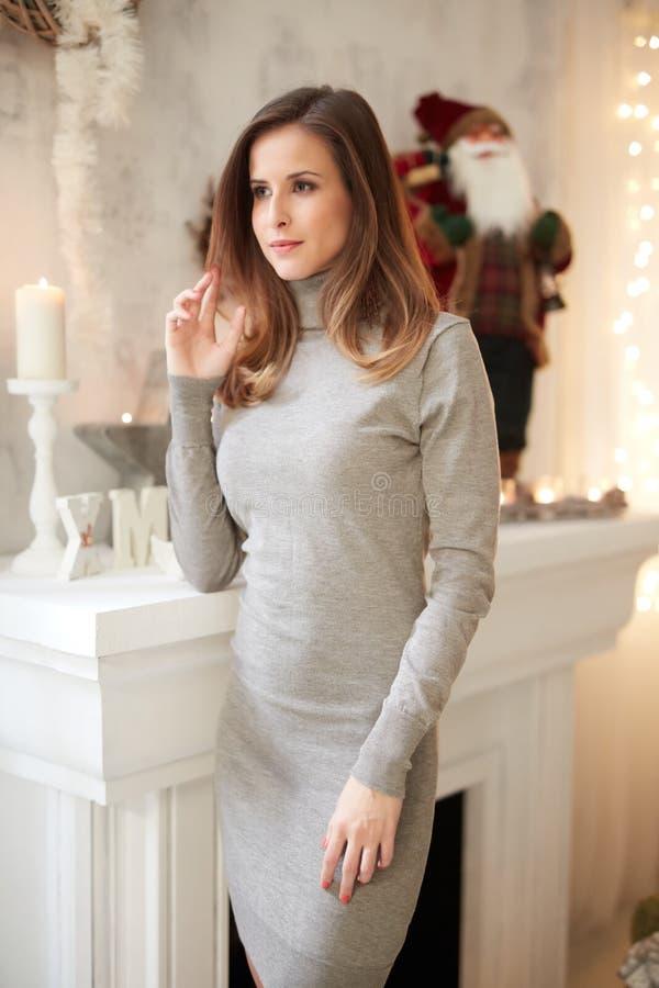 Jovem mulher elegante na chaminé no tempo do Natal fotografia de stock royalty free