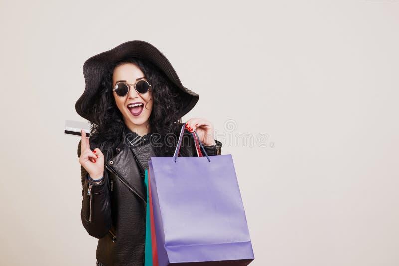 Jovem mulher elegante no chapéu negro com cartão de crédito e em uns sacos de compras coloridos sobre o fundo branco do estúdio imagens de stock royalty free