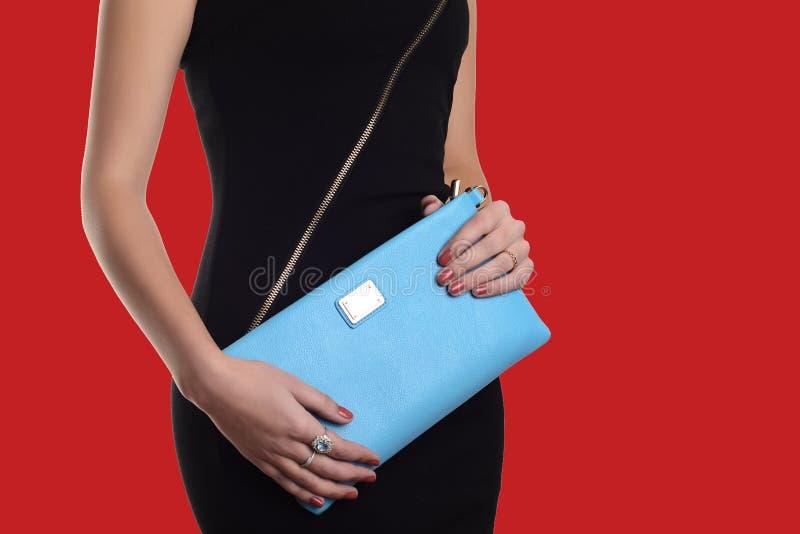 A jovem mulher elegante no vestido preto que guarda a embreagem azul Fundo vermelho foto de stock royalty free