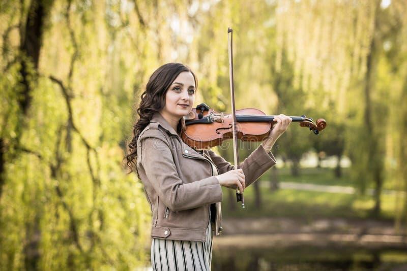 A jovem mulher elegante pensativamente e joga sonhadoramente o violino no parque fotos de stock royalty free