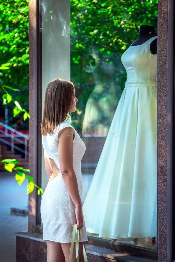 Jovem mulher elegante que admira o vestido de casamento branco bonito na janela de mostra do boutique nupcial foto de stock