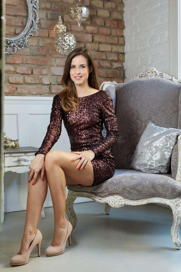 Jovem mulher elegante que senta-se na poltrona imagens de stock royalty free