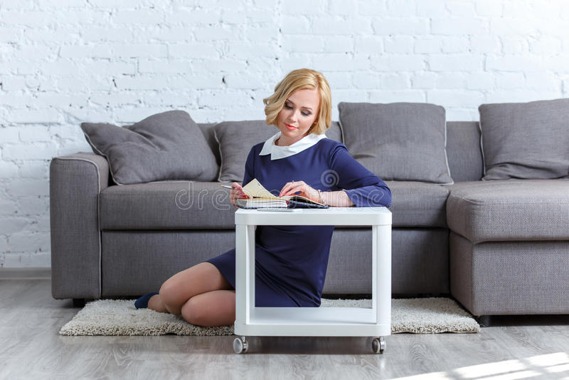Jovem mulher elegante que senta-se no tapete com seu diário imagens de stock royalty free