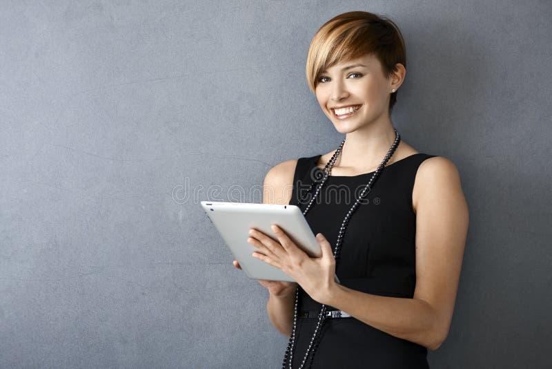 Jovem mulher elegante que usa a tabuleta que inclina-se à parede fotografia de stock royalty free