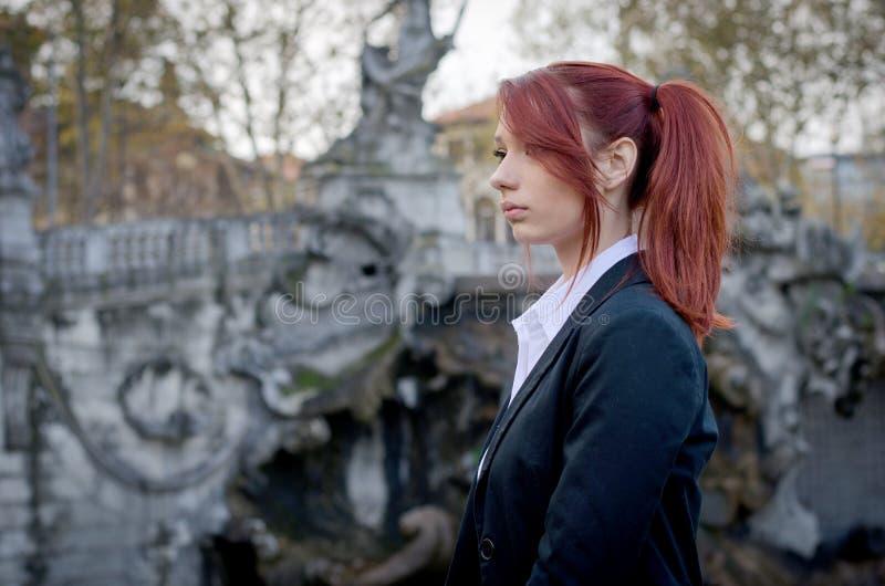 Jovem mulher elegante, revestimento vermelho-dirigido, vestindo imagem de stock royalty free