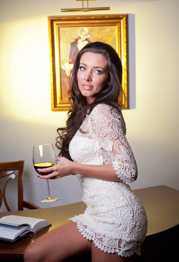 Jovem mulher elegante sensual no vestido branco que guardara um vidro de vinho foto de stock