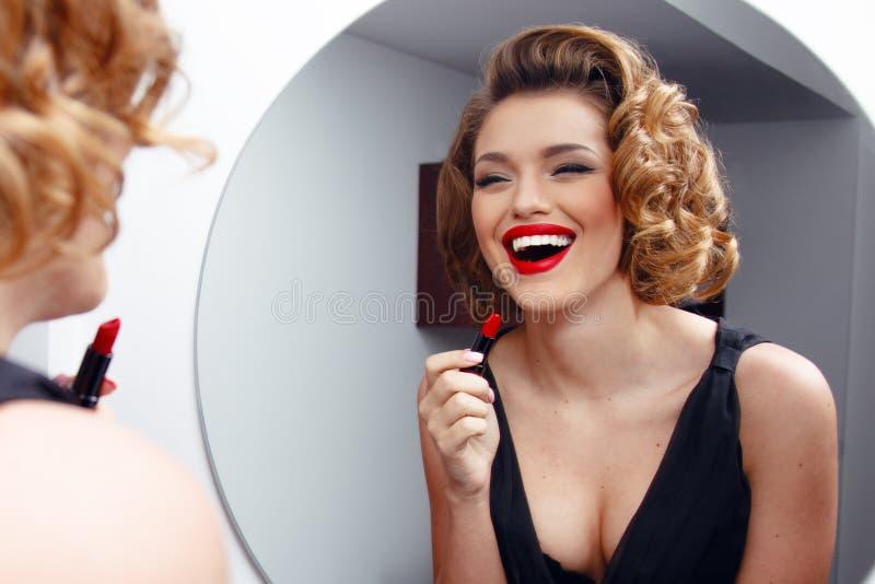 A jovem mulher elegante, sorrindo, o modelo com penteado de encantamento e a noite compõem, aplicando o batom vermelho nos bordos imagens de stock royalty free