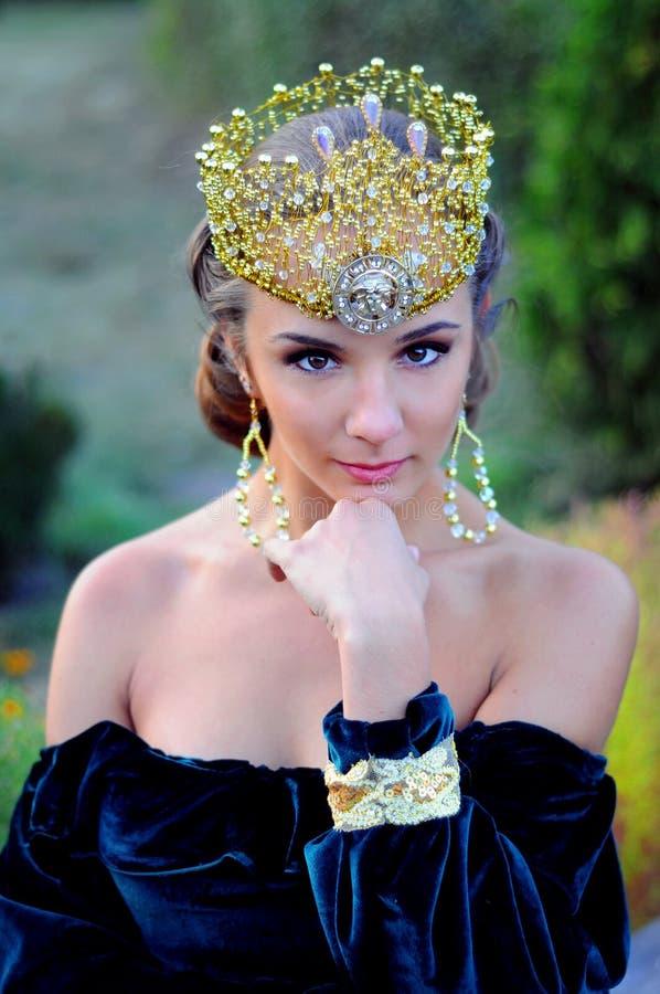 Jovem mulher elegante vestida como a rainha imagens de stock royalty free