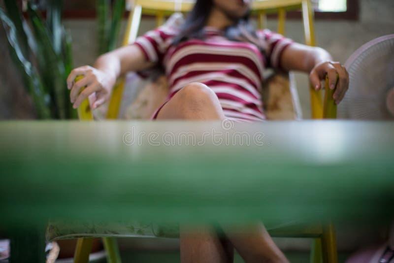 Jovem mulher em casa que dorme na cadeira moderna imagem de stock
