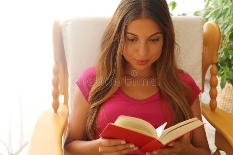 Jovem mulher em casa que senta-se na cadeira confortável que relaxa em seu livro de leitura da sala de visitas foto de stock
